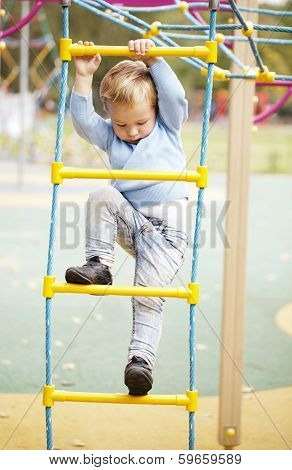 Cute little boy climbing on a jungle gym