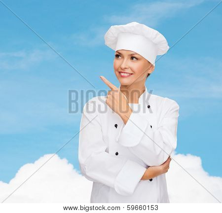cooking, advertisement and food concept - smiling female chef, cook or baker pointing finger to something