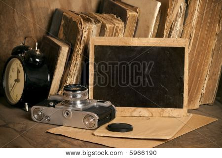 Vintage photo frame, with old books, clock and photo camera.