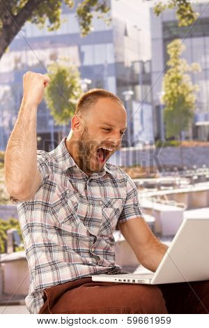 Young man using laptop, shouting happy with clenched fist.