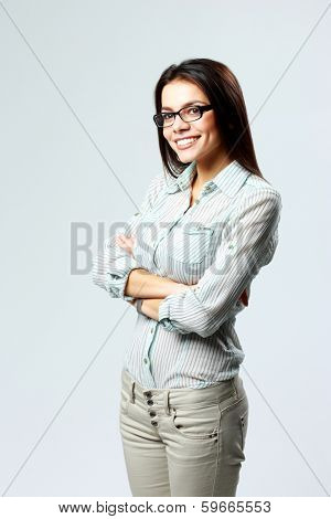 Young smiling woman standing and looking away on gray background