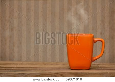 Orange Mug On A Wooden Table Over Grunge Wallpaper