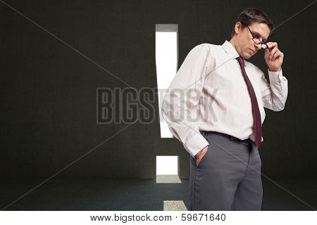 Thinking businessman touching his glasses against grey room with exclamation mark door