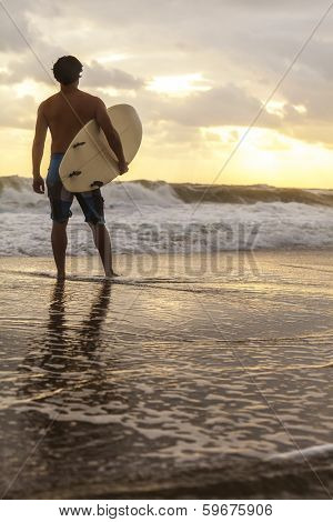 Rear view of male surfer with white surfboard standing on a beach at sunset or sunrise