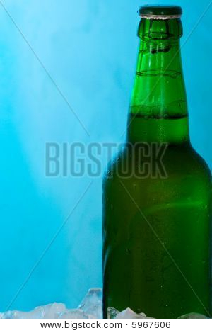 Green Bottle Of Beer And Ice On Abstract Blue Background