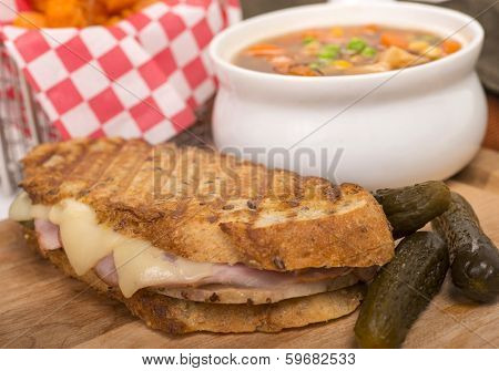 Delicious panini made with ham, pork and swiss cheese served with a vegetable soup, sweet potato fries and pickles