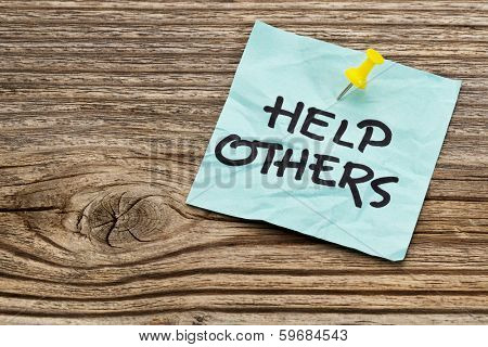 help others  reminder note against grained weathered wood