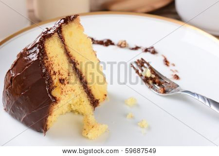 A slice of yellow cake with chocolate frosting with a piece missing. The white plate and fork have crumbs and frosting.