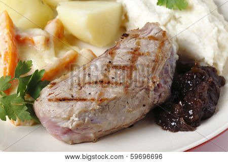 Veal sirloin steak with onion marmalade, celeriac puree, julienned carrots in a white sauce and boiled potatoes, garnished with parsley.