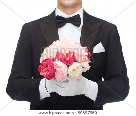 wedding, anniversary, special occasion concept - close up of man in tail-coat with bouquet of roses or peonies