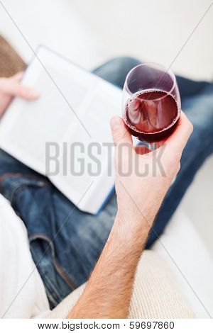 leisure, drinks, education and lifestyle concept - close up of male hand holdind book and glass of red wine