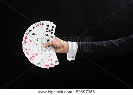magic, performance, circus, gambling, casino, poker, show concept - close up of magician hand holding playing cards