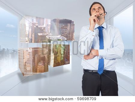 Thinking businessman biting glasses against bright white hall with windows