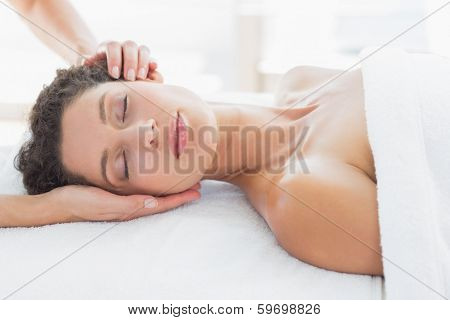 Beautiful young woman receiving head massage in health spa