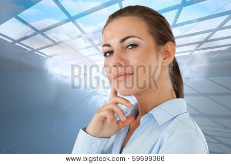 Side view of thinking young businesswoman against room with holographic cloud