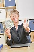 Happy winning business woman holding dollar bills and thumbs up