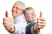 Happy elderly senior couple holding their thumbs up