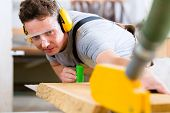 picture of workplace safety  - Carpenter working on an electric buzz saw cutting some boards - JPG