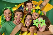 stock photo of excite  - Happy group of Brazilian sport soccer fans amazed celebrating victory together - JPG