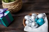 Silver and blue Easter eggs with giftbox on background