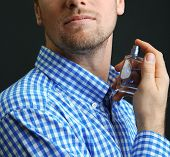 picture of perfume  - Handsome young man using perfume on black background - JPG