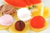 watermelon plum and slice of pineapple and chocolate and fruit ice cream on white plate isolated ove
