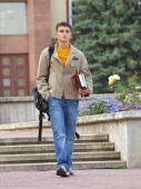 image of bagpack  - Student walks with bagpack and holds books - JPG