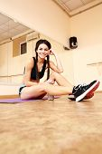 Young happy fit woman sitting on the floor at gym