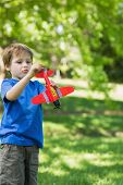 stock photo of aeroplan  - Cute young boy with toy aeroplane standing at the park - JPG