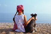 stock photo of schnauzer  - beautiful little girls embracing her dog looking at the sea