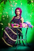 pic of loach  - Beautiful young woman sitting under an arch of flowers and overgrown loach - JPG