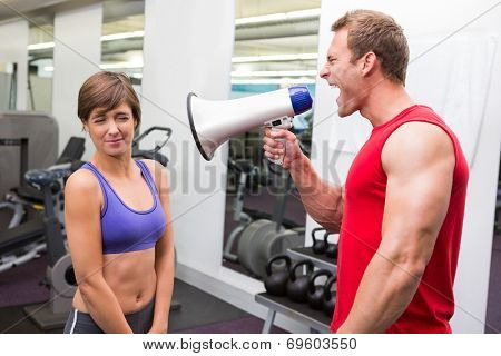 Personal trainer shouting at client through megaphone at the gym
