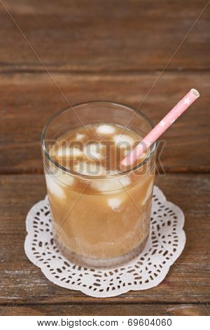 Iced coffee with milky ice cubes in glass on wooden background