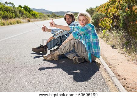 Attractive couple sitting on the road hitching a lift on a sunny day