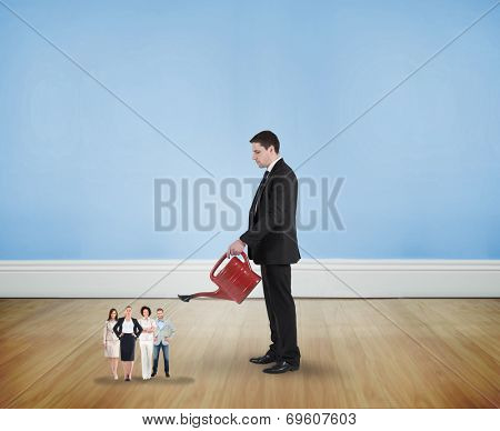 Businessman watering tiny business team against blue room with wooden floor