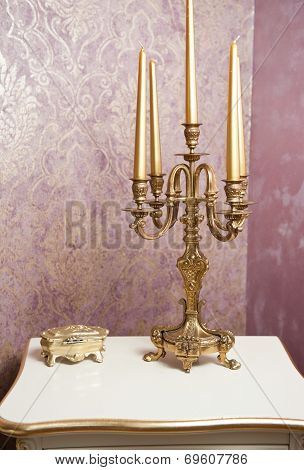 Golden candlestick with five candles on white table, in front of luxurious textured wall. Vintage