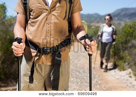Hiking couple walking on mountain trail with poles on a sunny day