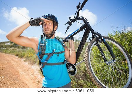 Fit man walking down trail holding mountain bike on a sunny day