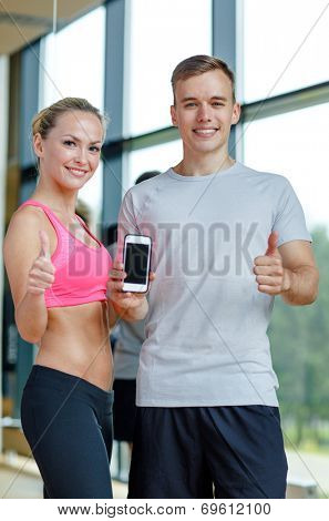 fitness, sport, advertising, technology and diet concept - smiling young woman and personal trainer with smartphone in gym showing thumbs up