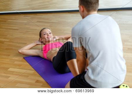 sport, fitness, lifestyle and people concept - smiling woman with male personal trainer exercising in gym