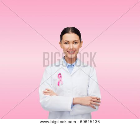 healthcare and medicine concept - smiling female doctor with pink cancer awareness ribbon over pink background