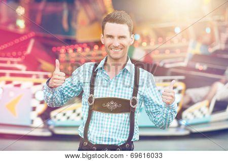 Beautiful man wearing traditional Bavarian Lederhosen doing thumbs up