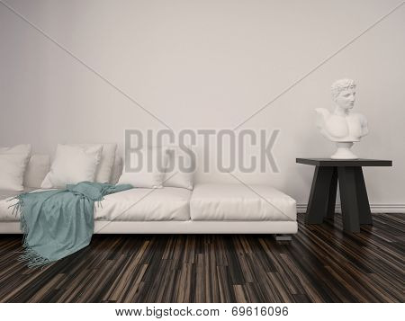 Interior decor in a classical living room with a white marble bust on a table alongside a comfortable upholstered white sofa with a blue throw rug against a white brick wall with parquet floor