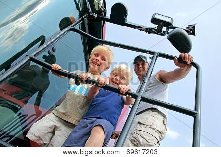 Children And Their Father Smiling As The Climb A Farm Tractor