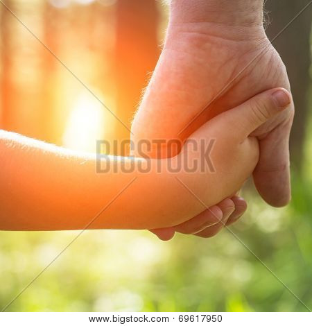 Hands, father with his son close-up, outdoors.