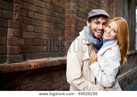 Portrait of affectionate couple in stylish clothes looking at camera outside
