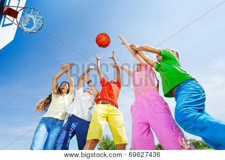 Kids playing basketball with a ball up in sky