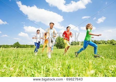 Excited kids playing and running in the field
