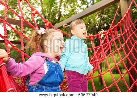 Girls screaming and standing on net of playground
