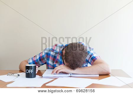 Young Adult Asleep Over Books Holding A Cup.